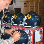 Joe Montana autographs his high school helmets for National Sports Distributors
