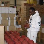 Jerry Rice autographing footballs for National Sports Distributors