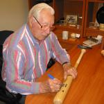 Bob Feller autographing bats at National Sports Distributors