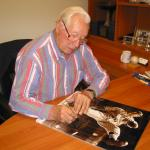 Bob Feller autographing photos for National Sports Distributors
