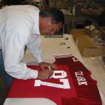 Dwight Clark autographing authentic jerseys for National Sports Distributors