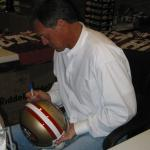 Dwight Clark autographing helmets for National Sports Distributors