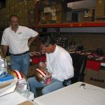 Dwight Clark autographing helmets at  National Sports Distributors