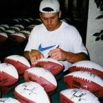 Mark Brunell autographing the white panel footballs designed by National Sports Distributors