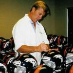 John Elway autographing helmets for National Sports Distributors