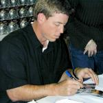 Troy Aikman autographing cards for National Sports Distributors