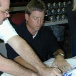 Troy Aikman autographing jerseys for National Sports Distributors