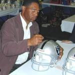 Marcus Allen autographing Raider Helmets for National Sports Distributors