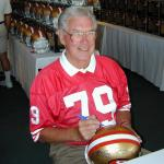 Bob St Claire autographing helmets for National Sports Distributors