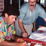 Steve Bono autographing jerseys for National Sports Distributors