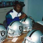 Tim Brown autographing helmets for National Sports