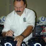 Dick Butkus autographing helmets for National Sports Distributors