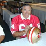 Dave Wilcox autographing helmets for National Sports Distributors