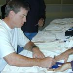 Troy Aikman autographs his Dallas Cowboys jerseys for National Sports Distributors