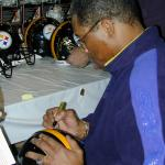Dwight White autographing Steel Curtain helmets for National Sports Distributors