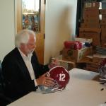 Ken Stabler signing helmets for National Sports Distributors