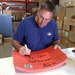Dwight Clark signing Candlestick Park seatback at NSD warehouse