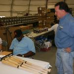 Willie McCovey autographing bats for National Sports Distributors