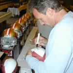 Joe Montana autographing footballs for National Sports Distributors