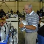 Daryl Lamonica autographing helmets for National Sports Distributors