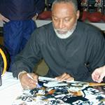 LC Greenwood autographing Steel Curtain 16x20 photos for National Sports Distributors