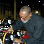 LC Greenwood autographing Steel Curtain helmets for National Sports Distributors