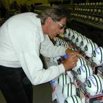 Joe Namath autographing mini helmets for National Sports Distributors
