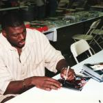 Larry Johnson autographs photos for National Sports Distributors