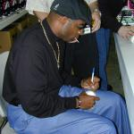 Deion Sanders autographing baseballs for National Sports Distributors