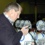 Johnny Unitas autographing helmets for National Sports Distributors