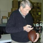 Johnny Unitas autographing Throwback Duke Footballs for National Sports Distributors