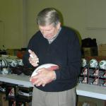 Johnny Unitas autographing footballs for National Sports Distributors