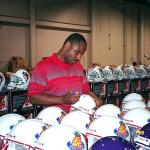 Warren Moon autograping helmets for National Sports Distributors