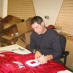 Steve Young autographing jerseys for National Sports Distributors