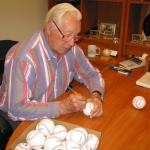 Bob Feller signing baseballs for National Sports Distributors