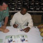 Cris Carter autographing 8x10 photos for National Sports Distributors