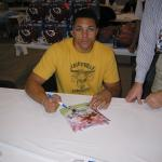 Tony Gonzalez autographing 8x10 photos for NSD