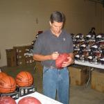 Trent Green autographing footballs for National Sports Distributors