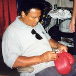 Muhammad Ali autographihng boxing gloves for National Sports Distributors