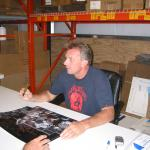 Joe Montana autographing 16x20 photos for National Sports Distributors
