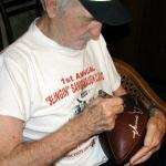 Sammy Baugh autographing Throwback Duke Footballs for National Sports Distributors