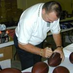 Dick Butkus autographing Throwback Duke Footballs for National Sports Distributors