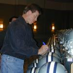 Troy Aikman autographs helmets for National Sports Distributors