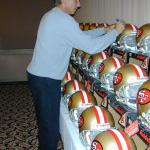 Joe Montana autographing helmets for National Sports Distributors