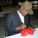 George Frazier autographing boxing gloves for National Sports Distributors