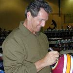 Joe Theismann autographing helmets for National Sports Distributors