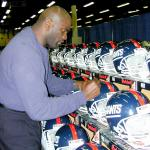 Lawrence Taylor autographing helmets for National Sports Distributors