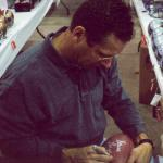 Steve Largent autographing footballs for National Sports Distributors