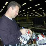 Howie Long autographing helmets for National Sports Distributors