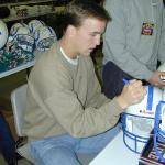 Peyton Manning autographing helmets for National Sports Distributors
